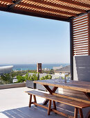 Wooden table and bench on roofed terrace with sea view