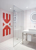 Red and white wall tiles and glass partition wall in designer bathroom