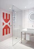 Designerbad mit rot-weißen Wandfliesen und Glastrennwand