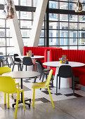 Runde Tische mit gelben und schwarzen Stühlen im Restaurant mit Glasfassade