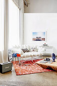 White cushion sofa on reddish carpet in front of window and wooden coffee table