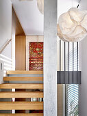 Designer pendant lamp in the stairwell with oak steps and concrete support