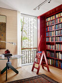 Red bookcase with matching ladder, seagrass wallpaper and round table in the library with oak parquet
