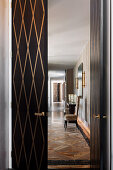 View through open double door with brass insert on chair with high back in elegant hallway