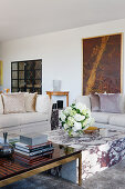 Books on ebony and brass coffee table, marble coffee table with bouquet of flowers, elegant sofa set in background
