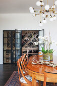 Oval dining table and chairs under vintage lamp, wine cabinet in background