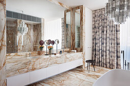 Bathroom with marble vanity, marble tiled floor and Murano glass chandelier above the bathtub