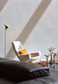 Pattern of light and shade on wall behind white designer armchair