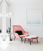 Designer-Sessel mit Fusshocker neben Stehlampe und Beistelltisch in Zimmerecke