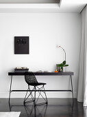 Small workplace with black table and designer chair on white wall