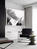 Upholstered chair and designer side table in front of black and white picture on the wall