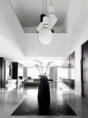 Designer pendant lamp over a round table with an orchid in an open living room with double room height