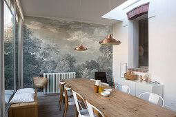Long wooden table and chairs in dining room with mural wallpaper