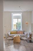 Polstersofa, Tischset und Klassikerstühle im Wohnzimmer