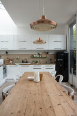 Long wooden table and chairs in white, open-plan kitchen