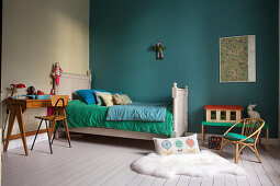 Bed, desk and chair in child's bedroom with turquoise wall