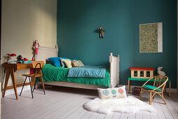Bett, Schreibtisch und Stuhl im Kinderzimmer mit grüner Wand