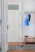 Blick durch offene Tür in den Flur mit grafisch gemustertem Teppich