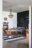 Runder Tisch mit Rattanstühlen unter Kronleuchter, im Hintergrund Sofa vor Tafelwand