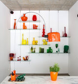 Murano glassware on glass shelves and arc lamp with orange shade