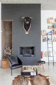 Tierfellteppich, Beistelltisch und schwarzer Stuhl vor schwarzer Wand mit Stierkopf und Kamin