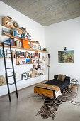 Wandregale mit Bibliotheksleiter und Daybed auf Zebrafell in hellem Wohnraum mit Betondecke und Betonboden