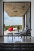 Eleganter Stuhl mit Fussschemel und Beistelltisch vor Glaselement, Blick auf die Terrasse