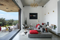 Grey sofa set with red scatter cushions in living room opening onto terrace