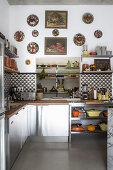 Kitchen counters, cement-tiled splashback and collection of decorative plates on wall above