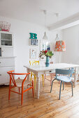 Various colourful chair at white dining table on wooden floor