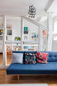 Blue sofa in front of half-timber frame with view into dining room