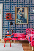 Pink, patterned sofa below painting on wall with blue, patterned wallpaper