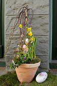 Potted pussy willow decorated with Easter eggs, narcissus and moss next to Easter egg by front door