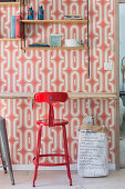 Vintage stool at rustic desk below shelves mounted on wall with red and white wallpaper