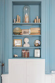 Pictures, busts and ornaments on shelves in grey-blue niche