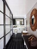 Blick vom Flur mit Sitzbank und Wandspiegel auf Waschtisch mit Aufsatzbecken