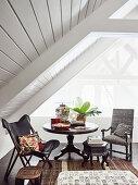 Sitzplatz mit rundem Tisch und zwei Stühlen unter dem Dach