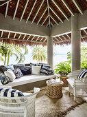 Outdoormöbel mit blau-weiß gemusterten Kisssen auf überdachter Terrasse mit Meerblick