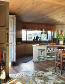 Counter, wooden ceiling and cowhide rug in open-plan kitchen