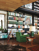 Lamp on antique table and green armchair in front of bookcase