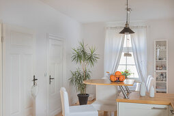 Semicircular breakfast bar on end of kitchen counter in white kitchen of converted dairy