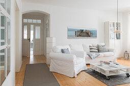 White, loose-covered sofa set, pallet coffee table and pale wooden floor in living room of converted dairy