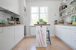 Narrow island counter in white kitchen with open shelving