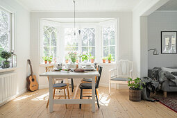 White dining table with various chairs in front of bay window