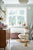 Graphic wallpaper and vintage-style furniture in bright child's bedroom
