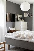 Blick ins Schlafzimmer mit weißer Kommode und grauen Wänden