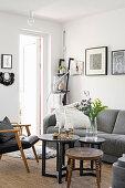 Coffeetable, Lederstuhl und graues Polstersofa im Wohnzimmer mit weißer Wand