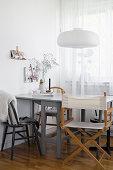 Grauer Esstisch mit verschiedenen Stühlen vor dem Fenster