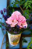 Hängender, kleiner Eimer mit Rosen und Lavendelblüten