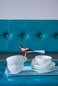 Tablett mit Geschirr und Dekovogel auf einem blauen Sofa
